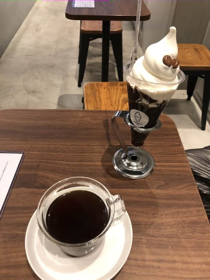 Photograph of a black coffee on a wooden table with a coffee ice cream