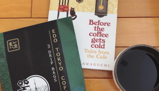 Photograph of a bag of coffee, a book on coffee, and a black coffee