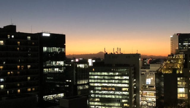 A view of Tokyo with Mt Fuji in the background against the sunset